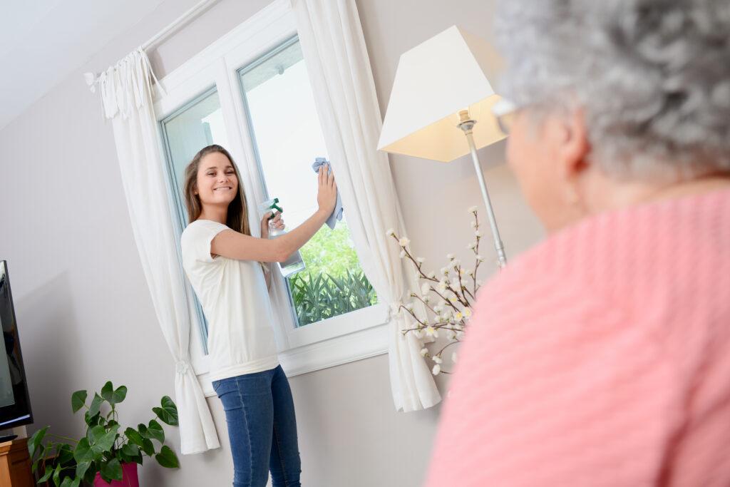 Junge Frau putzt für ältere Dame Fenster