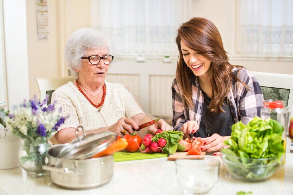 Junge Frau hilft älterer Dame beim Kochen