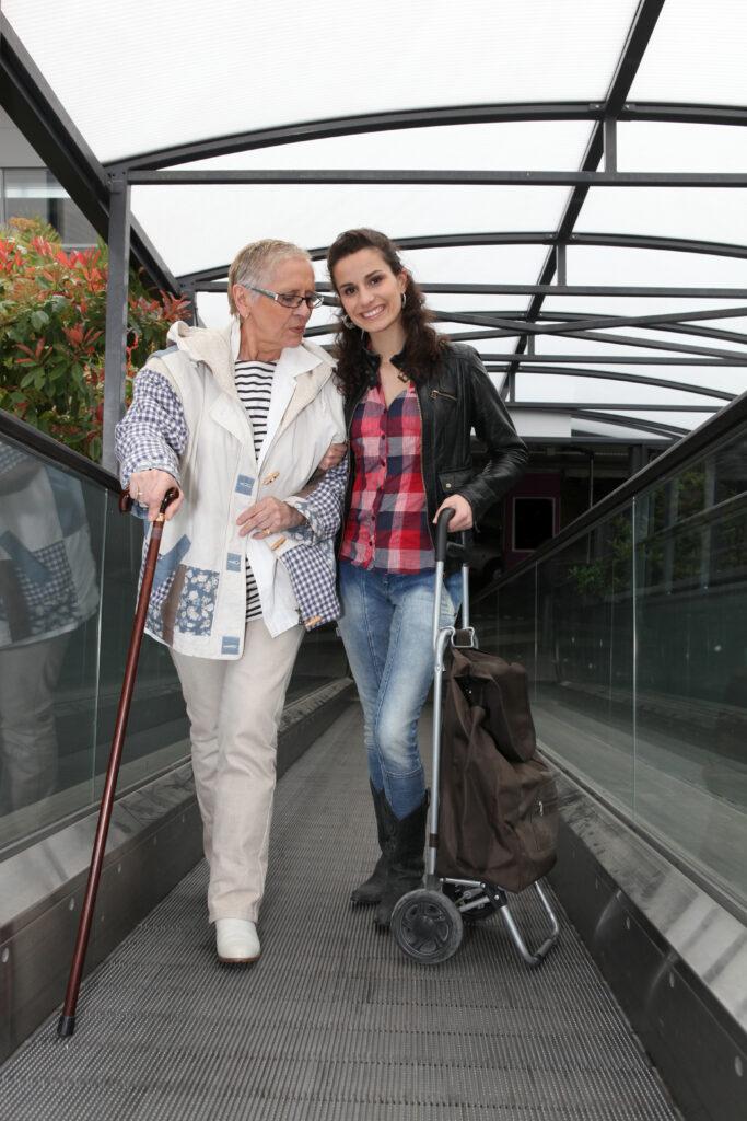 Junge Frau hilft älterer Dame beim Einkauf